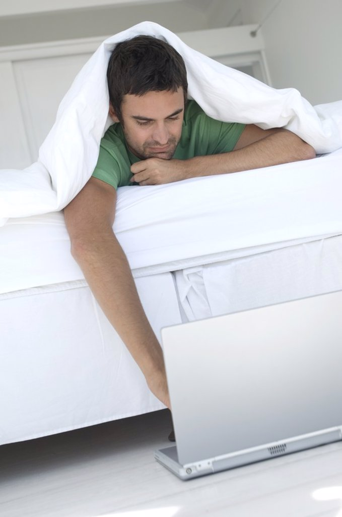 Young man using laptop in bed : Stock Photo