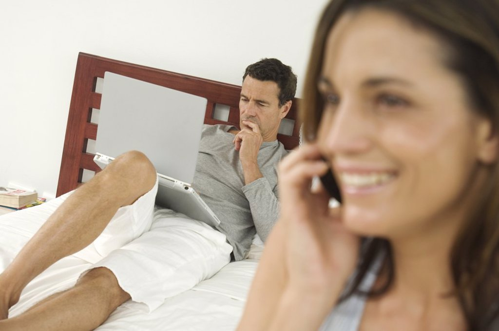 Woman using mobile phone, man on bed using laptop in background : Stock Photo