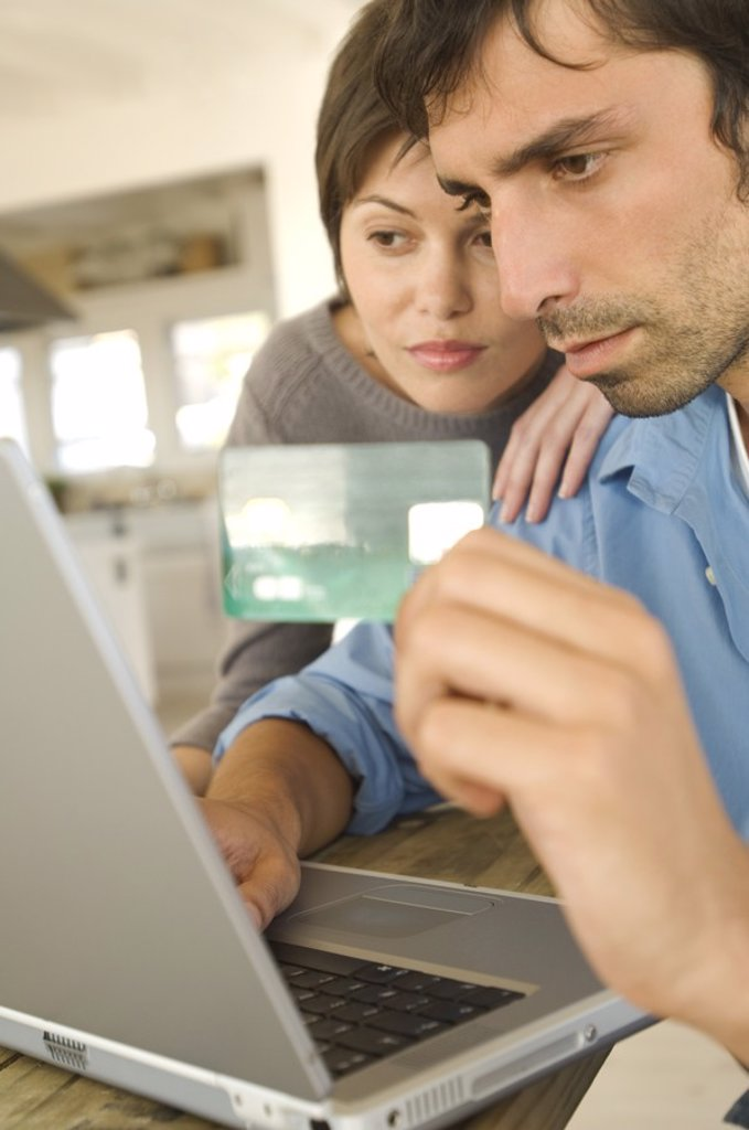 Stock Photo: 1738R-4067 Young couple using credit card on internet