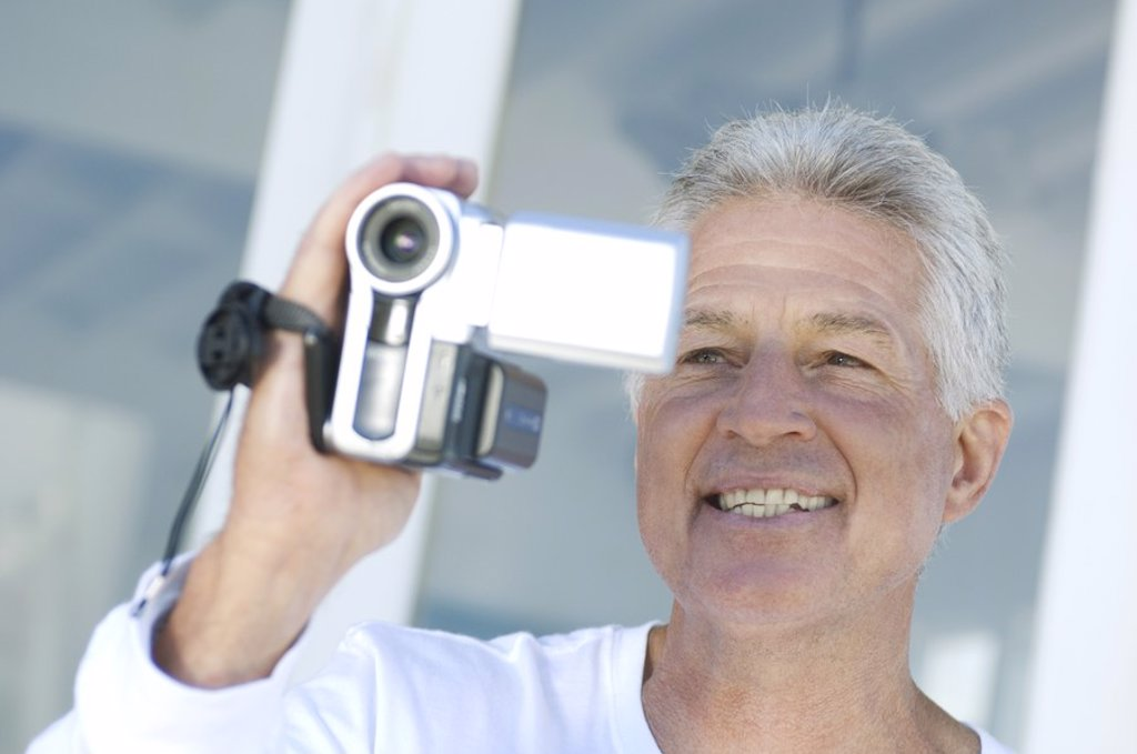 Stock Photo: 1738R-4069 Portrait of a man using camcorder