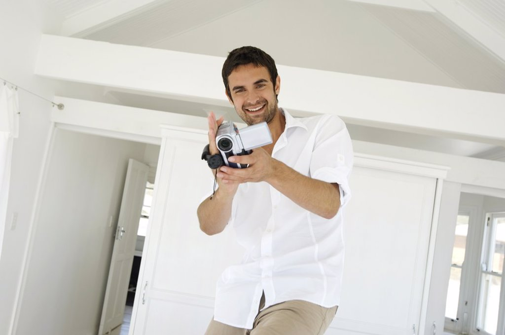 Stock Photo: 1738R-4071 Young man using camcorder