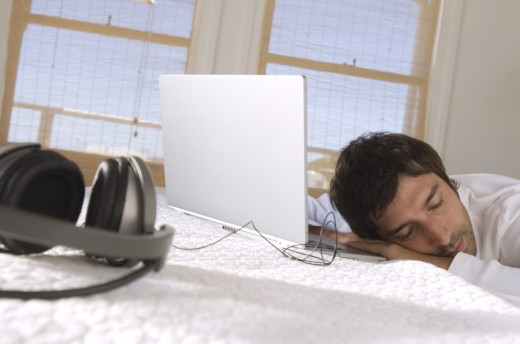 Young man sleeping in front of laptop : Stock Photo
