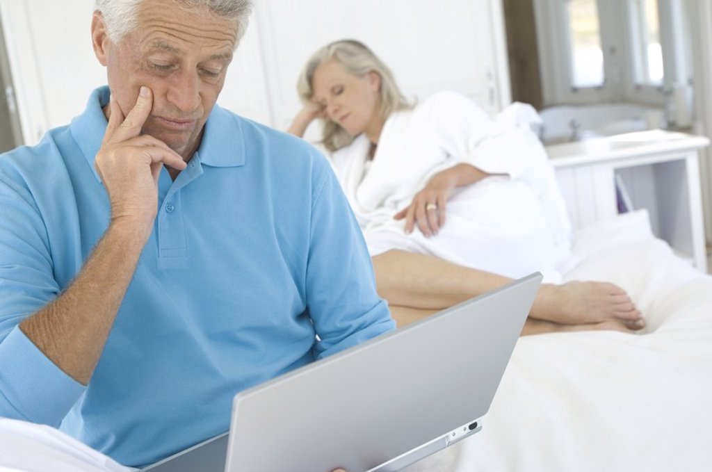 Man using laptop in bedroom, woman in background : Stock Photo
