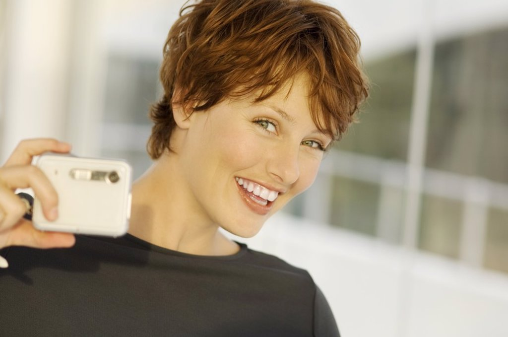 Stock Photo: 1738R-4076 Portrait of a young woman using digital camera