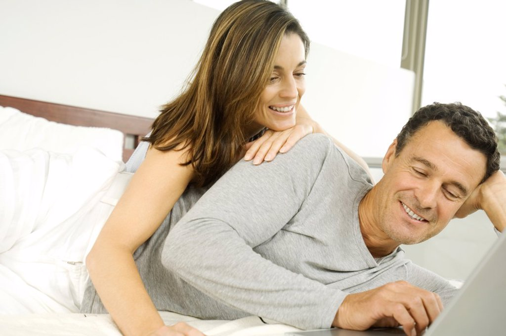 Stock Photo: 1738R-4079 Couple in bed, using laptop