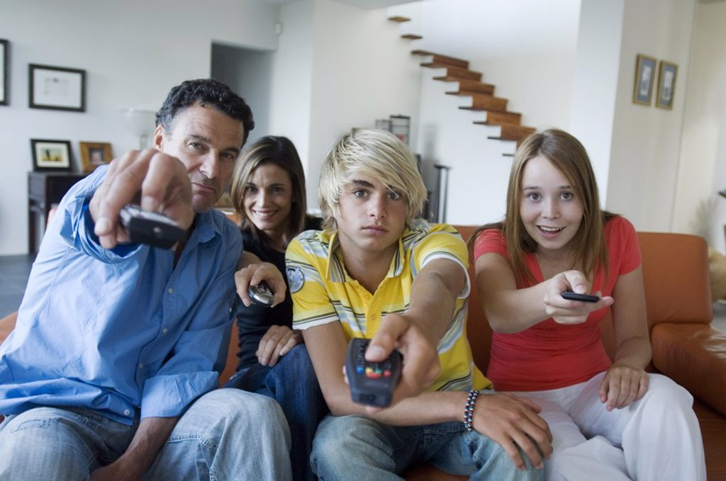 Parents and 2 teens using remote-controls : Stock Photo