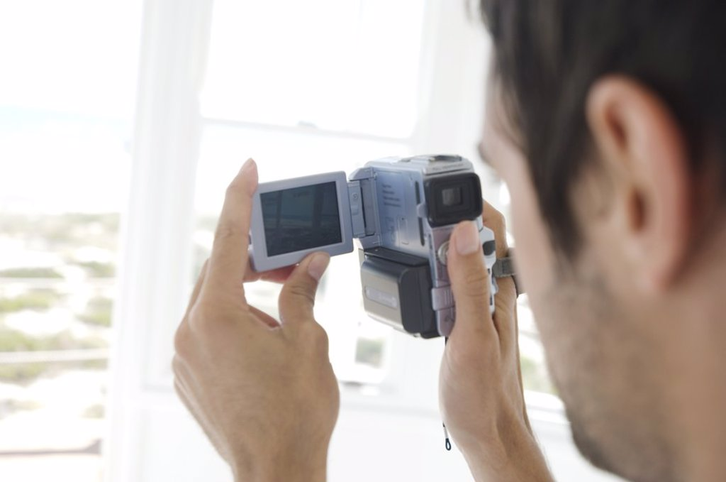 Young man using camcorder : Stock Photo