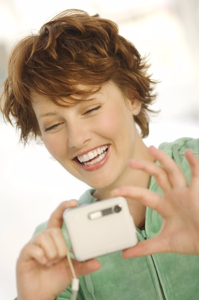 Portrait of a young woman using digital camera : Stock Photo