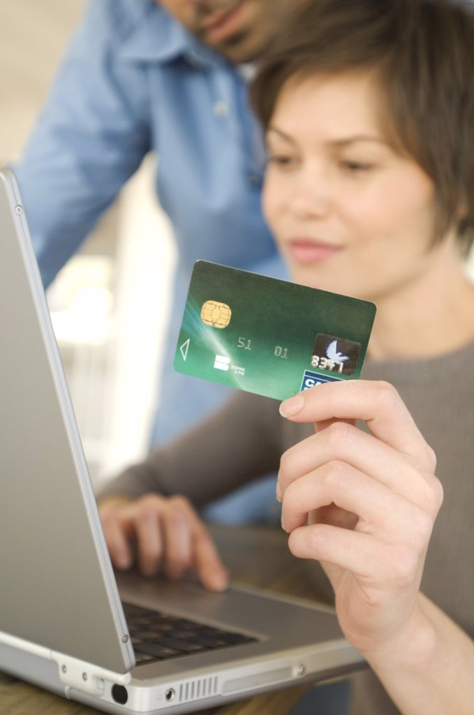 Stock Photo: 1738R-4089 Young couple using credit card on internet