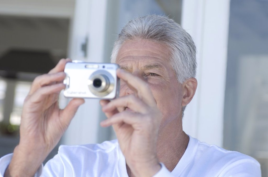 Portrait of a man using digital camera : Stock Photo
