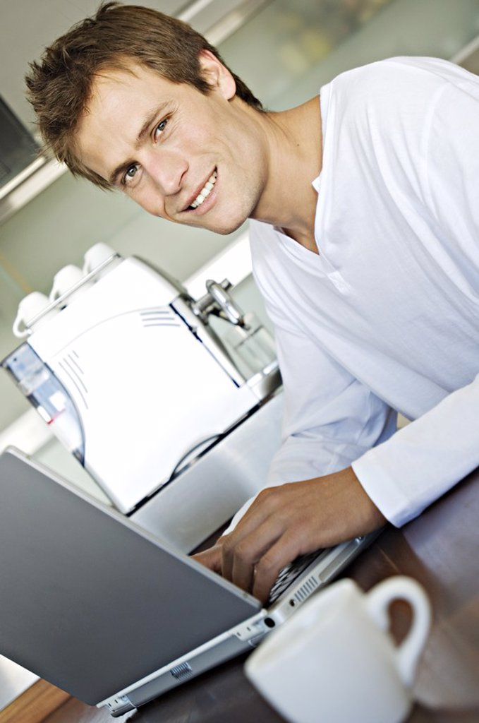 Young man using laptop in kitchen : Stock Photo