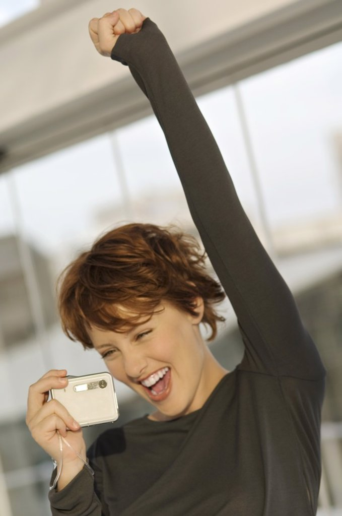 Stock Photo: 1738R-4094 Portrait of a young woman using digital camera