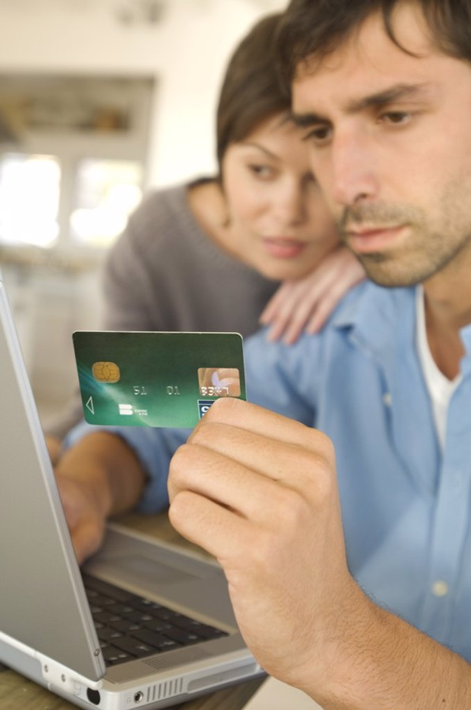 Stock Photo: 1738R-4095 Young couple using credit card on internet