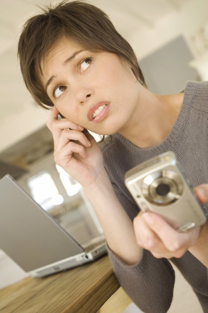 Stock Photo: 1738R-4096 Young woman phoning, holding digital camera