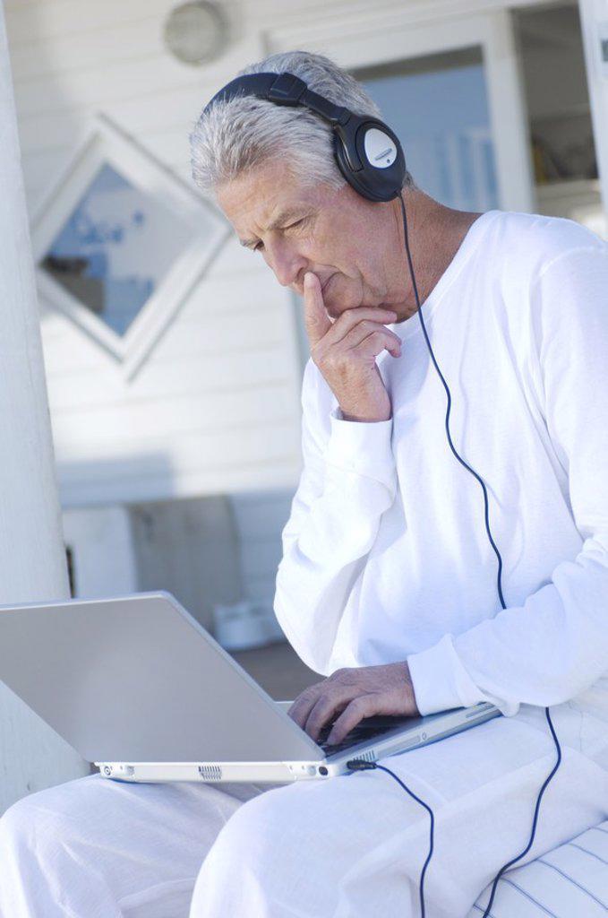Man with headphones using laptop : Stock Photo