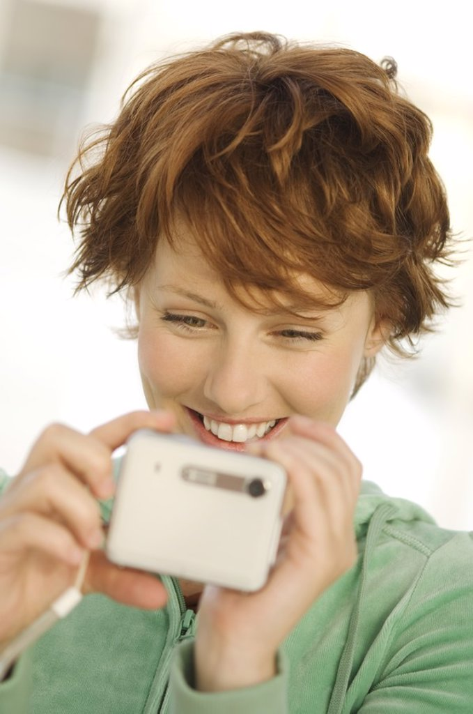 Stock Photo: 1738R-4105 Portrait of a young woman using digital camera