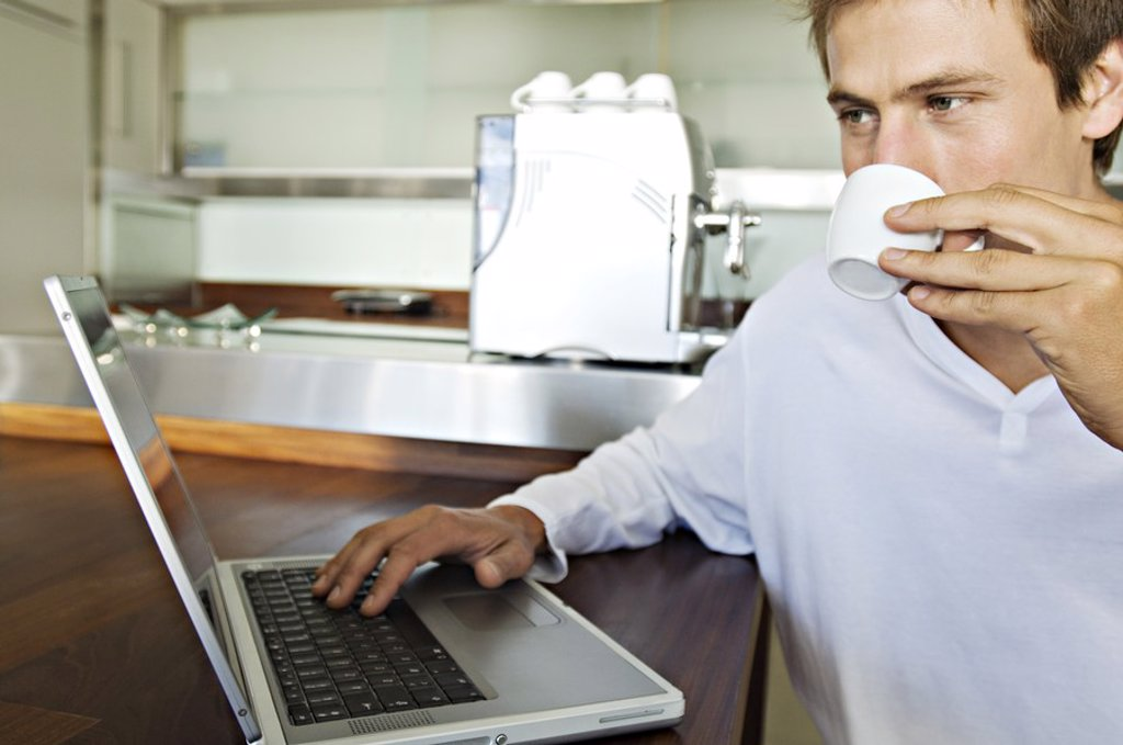Stock Photo: 1738R-4107 Young man using laptop in kitchen