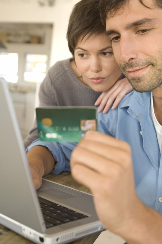 Stock Photo: 1738R-4108 Young couple using credit card on internet