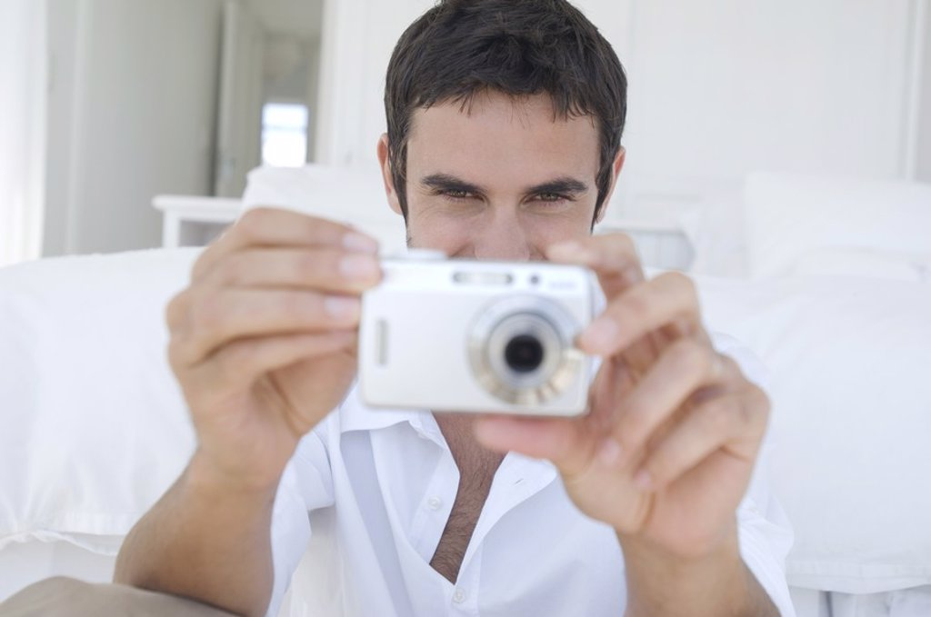 Young man using digital camera : Stock Photo