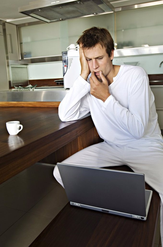 Stock Photo: 1738R-4110 Young man using laptop in kitchen