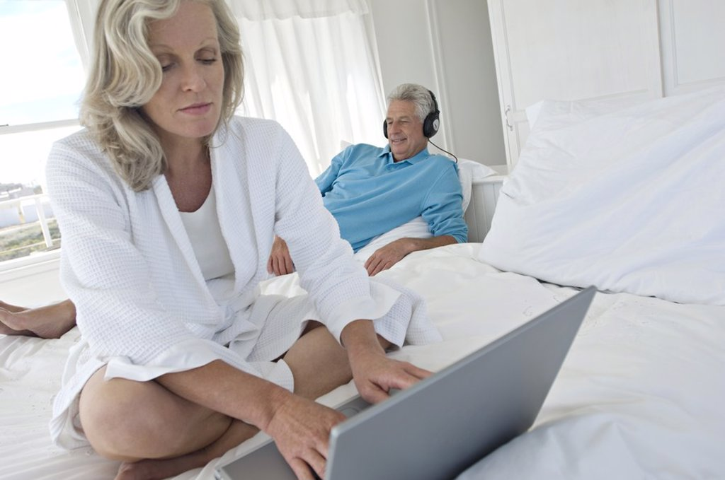 Woman using laptop in bedroom, man with headphones in background : Stock Photo