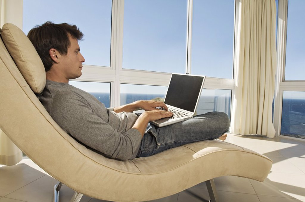 Young man using laptop in armchair : Stock Photo