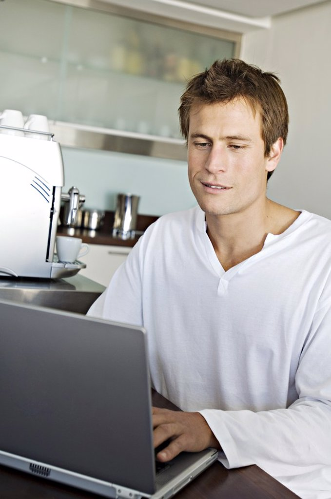 Stock Photo: 1738R-4114 Young man using laptop in kitchen
