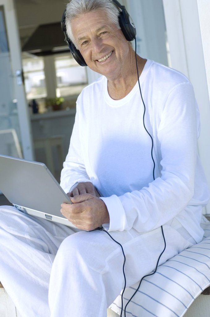 Smiling man with headphones using laptop : Stock Photo