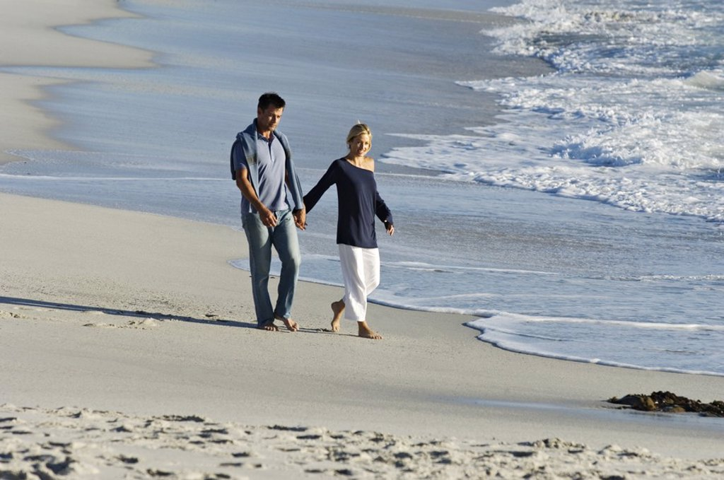 Couple holding hands, walking on the beach : Stock Photo