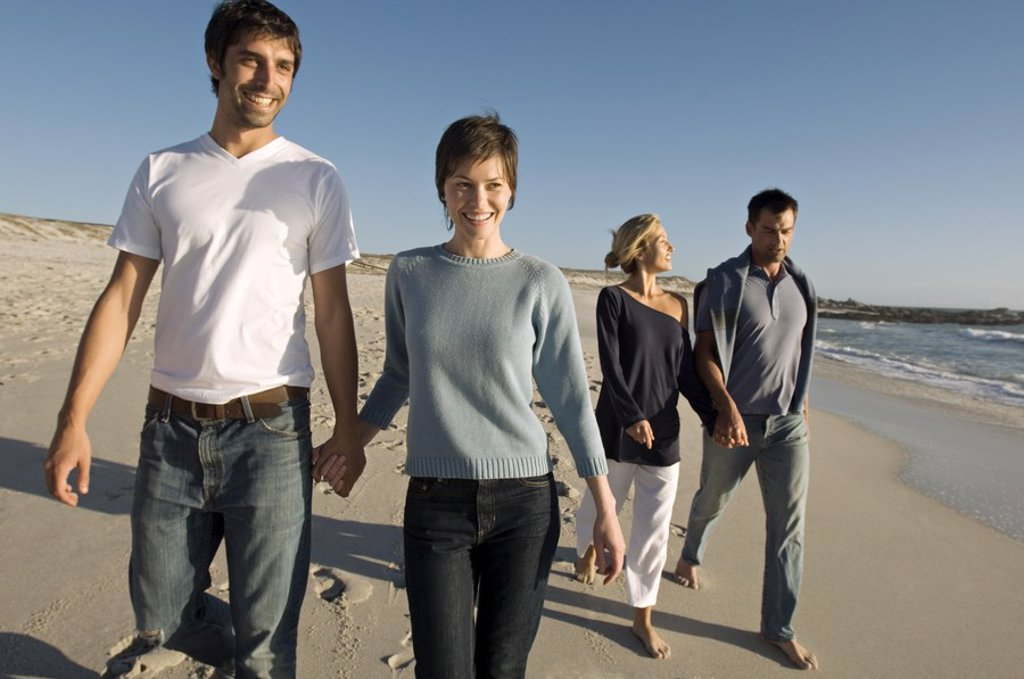 2 couples walking on the beach : Stock Photo
