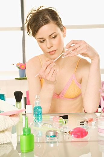 Young woman in underwear with make-up brush : Stock Photo