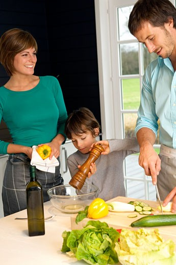 Mid adult man and a young woman preparing food with their son : Stock Photo