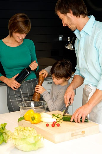 Stock Photo: 1738R-7015 Mid adult man and a young woman preparing food with their son