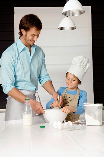 Mid adult man making a cake with his son in the kitchen : Stock Photo