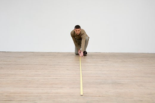 Interior designer measuring the hardwood floor with a tape measure : Stock Photo