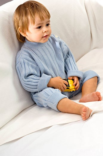 Stock Photo: 1738R-7307 Baby boy sitting on a couch and holding a toy car
