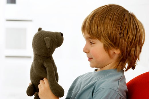 Side profile of a boy holding a teddy bear : Stock Photo