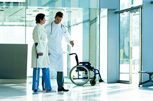 Male doctor assisting a female patient in walking on crutches : Stock Photo