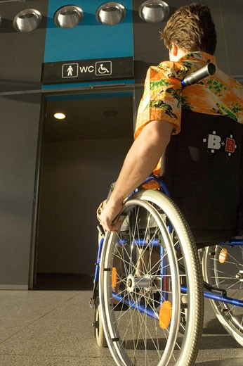 Rear view of a mid adult man sitting in a wheelchair : Stock Photo