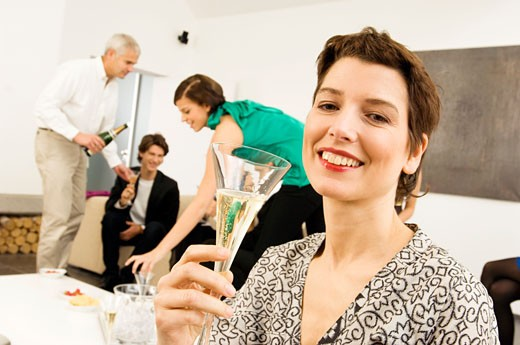Mid adult woman holding a wine glass with three people in the background : Stock Photo