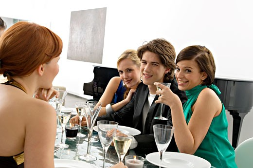 Portrait of a teenage boy with his friends at a dinner party : Stock Photo