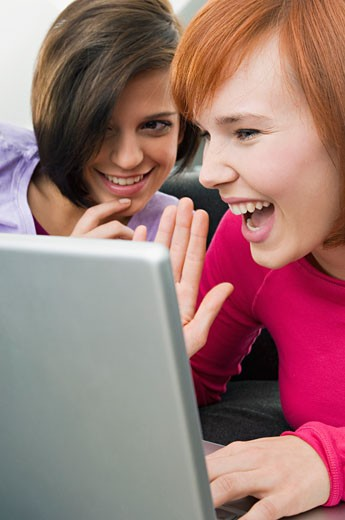 Two young women using a laptop : Stock Photo