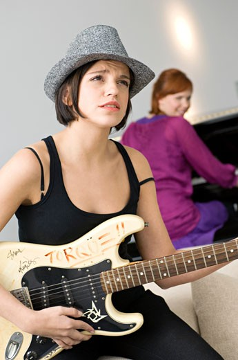 Young woman playing a guitar : Stock Photo