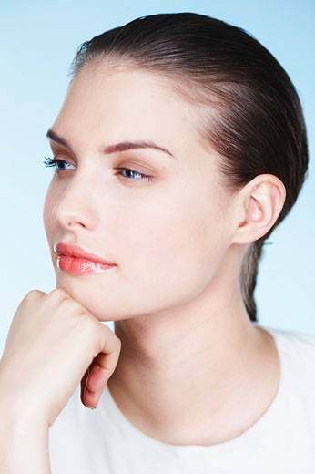 Portrait of young woman with hand on chin : Stock Photo