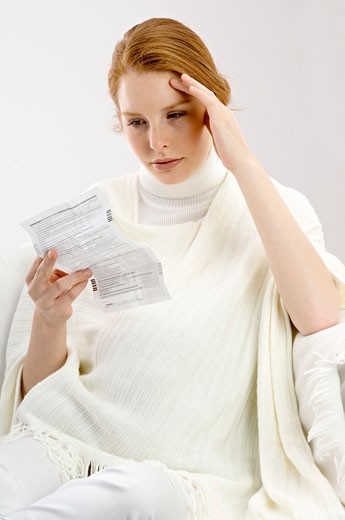 Stock Photo: 1738R-8560 Close-up of a pregnant young woman reading a medical report