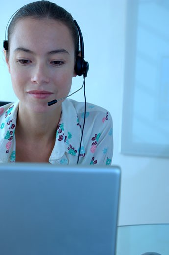 Young businesswoman wearing headset, close-up : Stock Photo