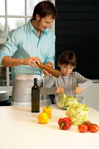 Mid adult man preparing food with his son in the kitchen : Stock Photo