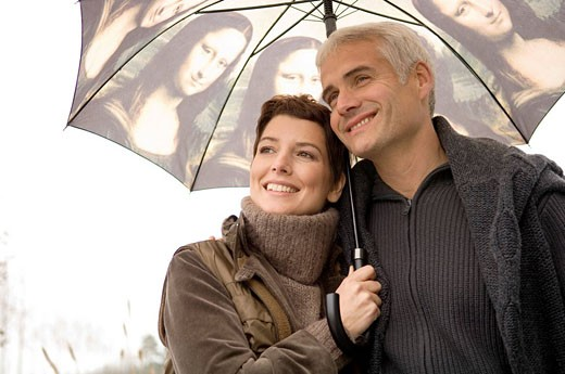 Close_up of a mid adult woman and a mature man under an umbrella : Stock Photo