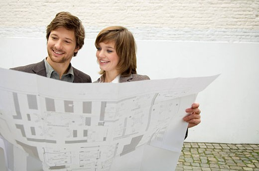 Mid adult man and a young woman looking at a blueprint : Stock Photo