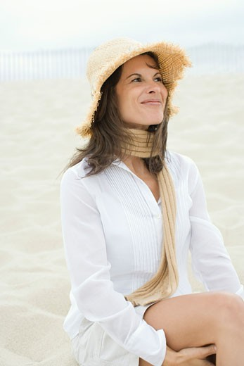 Mature woman sitting on the beach and smirking : Stock Photo